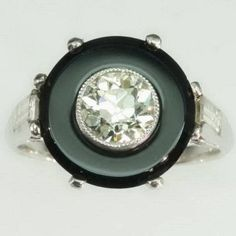Art Deco engagement ring in platinum featuring a black French jet circle and 1.47 carats diamonds. The center diamonds is one old mine brilliant cut diamond of 0.91 carat (color approx. J/K, clarity approx. vs) and set with two baguette cut diamonds of 0.50 carat and four single brilliant cut diamonds of 0.06 carats.
