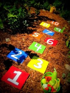 """Get concrete pavers at big box home store. Use Outdoor paints in red, purple orange, blue, green, yellow (whatever colors you like). The black was used to paint on the numbers and the black was to outline the numbers so they would """"pop."""" You'll probably need more of the white   than any other color.  Would make a great """"hop scotch"""" play area."""