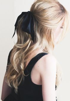 loose half-pony tied with a black bow