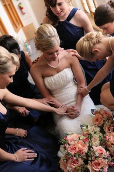 The bridesmaids praying over the bride before the ceremony. Just beautiful...
