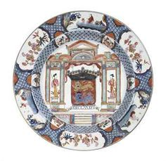"""A LARGE ROSE-IMARI """"PROVINCES"""" DISH / CIRCA 1725 / The arms of Frieslandt in the center, inscribed ERIEGLANDT, within elaborate architectural framework including two Chinese ladies standing in niches, all within cobalt blue diaper patterned reserved with small floral, aquatic and figural panels /50000"""