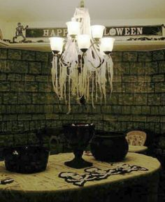 "Halloween indoor decor / party food table. Cheese cloth on the chandelier, muslin cut into strips to ""mummy wrap"" the table and scene setter wall coverings over the windows."