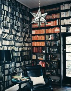 home library with shelves painted black, black leather furniture, dark wood floors, white trim and ceiling, and a leaded glass Moravian star pendant light