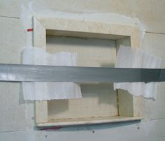 Step 11: Use duct tape to hold unit in place for 4 hours. Use paper (or something similar) to protect Niche from duct tape adhesive. Once dry, remove tape. Now you can cut and set tile within and around your Recessed Shower Wall Niche.