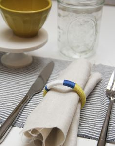 DIY napkin rings using any colored thread, hot glue gun, and a shower curtain ring!
