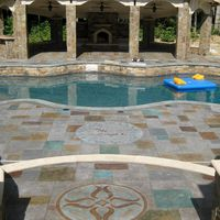 Two decorative concrete logos complete this stamped concrete pool deck's look.  Greystone Masonry Inc Stafford VA