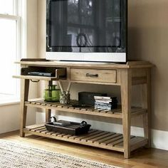 """Wood console table with a power outlet and 2 drop-front electronics compartments.  Product: Console tableConstruction Material: WoodColor: OatmealFeatures:Part of the Paula Deen Home Collection Two drop-front, pull-out drawers for electronicsTwo lower shelvesDistressed finishDimensions: 34"""" H x 58"""" W x 22"""" D"""