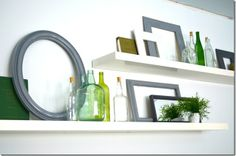 love the glass bottles, plants and empty frames