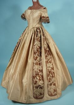 """Evening gown, circa 1860, shot taffetas and brocade, five pieces to this outfit, first two shown here, sleeves are edged in silk floss fringe, deep """"v"""" at front of bodice, laced back closure, padded bosom, cartridge pleats, brocade is then used in wide double panels on both sides of the skirt as faux sashes, may have been a wedding outfit, offered by Antique Dress"""
