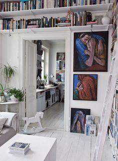 Una cocina en blanco llena de arte y objetos.  Vista cocina y caballito de madera