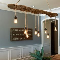 Lights hanging from a natural log, which is hung above a bar or table much light a pool table light. This would be beautiful using a polished, naturally-shaped cedar log with a poly coat, using uniformly hung pendant lights from it. Cut a wire channel out-of-sight along the top, and drill through for each pendant so the wire comes directly out of the log.