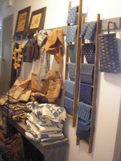 taylors*farmhouse*attic...a nice way to display indigo fabrics ....ladders on a shaker peg rack