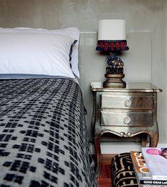 No quarto, as paredes de cor cinza emolduram o criado-mudo de alpaca indiana, da L'oeil, e a escultura chinesa transformada em abajur. Na ca...