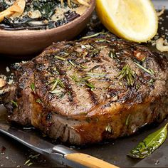 On a large platter drizzle steaks with a 2-count of olive oil (about 2 tablespoons). Season with salt and pepper. Remove the leaves from half of the rosemary and half of the thyme. Sprinkle  leaves on steaks; set aside. Preheat grill to medium-high. When the grill is ready, cook the rib-eyes about 7 minutes on each side for medium-rare. (Add another 2 minutes for medium.) Remove from grill and let stand for 5 minutes.
