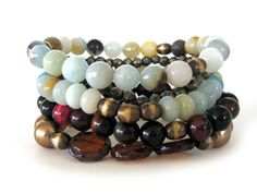 This is a gorgeous beaded stretch bracelets featuring 8mm round and rondelle amazonite with black tourmaline beads, 8mm multi colored tiger eye beads, oxidized brass beads, pyrite chunks, carmel colored Czech disc beads, and 10mm gold glass pearl beads handmade by Rock & Hardware Jewelry.