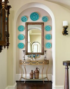 Turquoise oyster plates and a large clamshell lend eye-catching color to this hallway niche