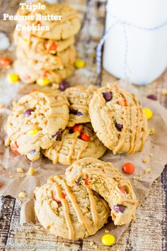Triple Peanut Butter Cookies filled with mini Reese's Pieces and drizzled with peanut butter for the ultimate peanut butter lovers cookie!