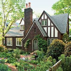 Cottage Courtyard Garden | These up-front flowers are woven into a tapestry of shrubs, roses, natives, herbs, and vines transforming the front yard of this Tudor cottage from boring to charming. | SouthernLiving.com