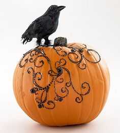 Rhinestone Pumpkin  Dress up a plain pumpkin with glittering black rhinestones and a fake feathered crow.