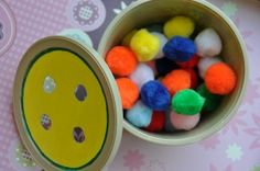 cut holes in lid of butter bowl. child pushes pom poms thru the holes (that are a little smaller than the pom pom). could add color matching circles to the lid.