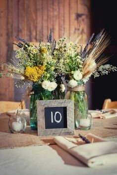 Wheat and Wildflower Centerpieces in Mason jars - are a great addition for a rustic wedding venue, like Silver Hearth Lodge. And don't you love the chalkboard table number too?!