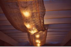 This is a cool idea for a porch or outdoor space.  Lights & burlap....cute!!!