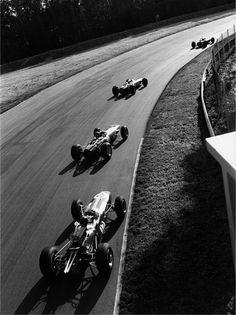 Italian Grand Prix, Monza, 1965. Jim Clark, eventual winner Jackie Stewart, Graham Hill and Dan Gurney drift through the Parabolica.