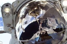 Space Shuttle astronaut Robert L. Satcher Jr., uses a digital still camera to take a picture of his helmet visor during mission's first mission outside the space station. Also visible in the reflections are various components of the station and astronaut Mike Foreman (upside down, top centre of picture)
