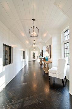 Herringbone wood floor, beadboard ceiling, walls.