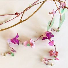 Radiant orchid necklace - a unique and versatile conversation piece.  This graceful lariat necklace highlites the color of the year and co-ordinating hues of pink, green and purple. It winds like a vine and features life-like Lucite flowers that are hand-dyed or painted and embellished with Swarovski crystals and silver toned pewter caps. $82