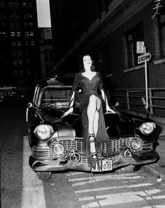 Maila Nurmi (Vampira) on the hood of her hearse, on a one way street.
