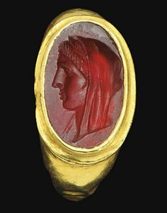 AN EGYPTIAN GOLD AND GARNET FINGER RING   PTOLEMAIC PERIOD, CIRCA 3RD CENTURY B.C.   The plain gold hoop flat on the interior, rounded on the exterior, expanding to the shoulders, the stepped oval bezel set with a flat stone engraved with the head of a woman, likely a Ptolemaic queen, in profile to the left, her himation pulled up over her head as a veil, a row of locks framing her face, with a strong jawline and a prominent nose ancient jewelleri, profil grand, de perfil, 400 ad, ancient art