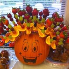 Fruit skewers stuck in pumpkin. Simple but fabulous idea. Good party snacks!