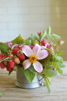 flowers with raspberries in a tin cup