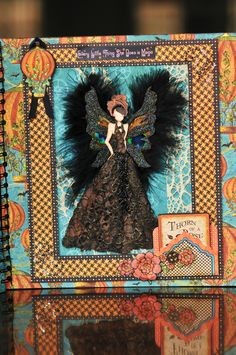 dark angel using Julie Nutting paper doll, lace, glitter, chip board wings, peacock feather eyes, rhinestones, black feathers and May arts woven web ribbon