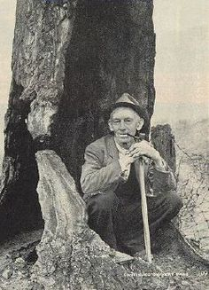 """L. Lawson Hatfield squats inside an old hollow tree which was long known as the """"stink tree,"""" where Hatfields were said to have stuffed dead bodies. (Usually they let them lie.) Devil Anse never repented his killings; he told Miss Thomas; """"A man has a right to protect his family."""""""