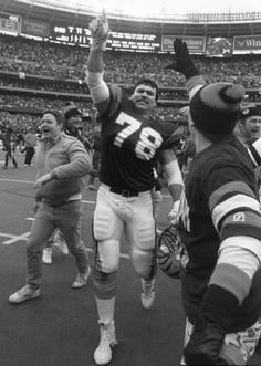 """JANUARY 8, 1989: Anthony Munoz at Riverfront Stadium, Cincinnati, Ohio. Walking off to chants of """"Who dey! Who dey! Who dey think gonna beat dem Bengals!"""" Anthony Munoz leaves the Jungle, the nickname for Riverfront Stadium when the Bengals roared to Super Bowl XXIII. The all-pro tackle responds with a """"We're No. 1"""" sign."""