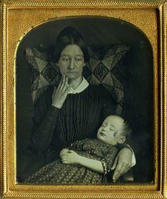A heartbroken woman holding her deceased child. Daguerrotype, 1850s