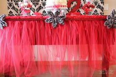 """DIY tuelle """"tutu"""" table skirt in pink.  Too young for an adult bridal shower?  Heck no.    10 yards of Tulle  Tablecloth  Ribbon  Pins"""