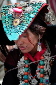 Ladakh - India > People   'Decorated Perak'  Rows of turquoise are often enhanced by a prominent ga'u, an amulet box sewed onto the center of the headdress. The outfit is further beautified by adding separate segments of decorated cloth. The perak is fastened onto a hairpiece made out of woolen braids, and the whole headdress is held in place on the owner's head by silver chains and stiff ear-flaps.   Caption and Image © Kieron Nelson