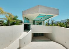 A rooftop swimming pool with a glass floor cantilevers out beside the entrance to this house in Marbella, Spain.