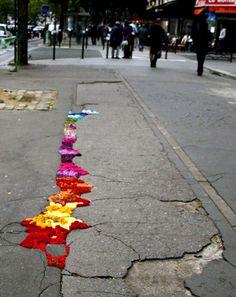 hand-dyed braided coils of yarn filling cracks and potholes along the streets of paris - juliana santacruz herrera