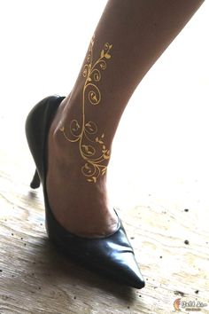 Wrap these lovely scrolling flowers around your ankle. The 24k gold tattoo is called Rebirth and can be found at GoldTattoosUS.com.