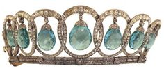 Queen Victoria Eugenia's Aquamarine Tiara current form - see close up pin. She gave it to her daughter, the Infanta Beatriz, who married Alessandro Torlonia, Prince of Civitella-Cesi, in 1935. In Beatriz's hands the tiara received its most extreme makeover, bringing it to the form we know today. It is strikingly similar to Queen Elizabeth's Grand Duchess Vladimir Tiara, but with aquamarine pendants rather than pearls or emeralds, and (like the Vladimir tiara) can be worn widowed, with no drops