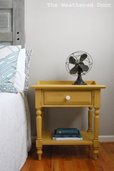 A mustard yellow nightstand with a milk glass knob