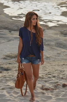 Ripped denim shorts with blue flowy off-the-shoulder shirt and long necklace