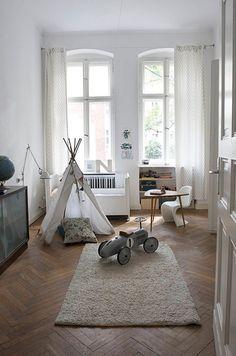 small playroom with herringbone floors and neutral furnishings.