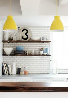 digging the rustic floating shelves, subway tile with gray grout, pops of yellow from the pendants.