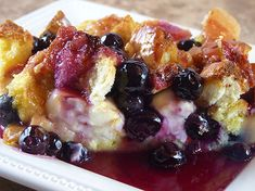 Blueberry & Cream Cheese Stuffed French Toast  For the French Toast: 1 loaf French bread, sliced and cubed 2 8-oz. packages cream cheese, cubed 1 cup blueberries 12 large eggs 1/2 cup maple syrup 2 cups milk For the Blueberry Syrup! 1 cup sugar 1 Tbsp cornstarch 1 cup water 1 cup fresh blueberries, rinsed and drained 1 Tbsp butte