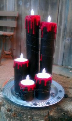 Getting ready for Halloween pillar candles using paper towel roles, hot glue, paint, plastic plate that's been painted and some battery operated tea lights